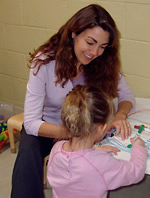 Photo of an art therapist working with a child making a painting