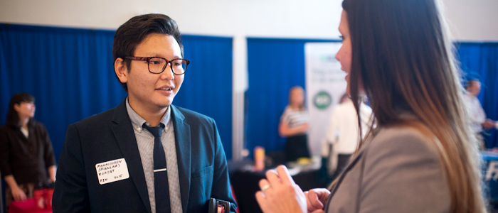 Photo of a business administration student talking to a recruiter at a job networking event
