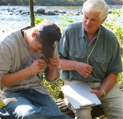 Photo of a student and a faculty member examining a plant specimen in the field