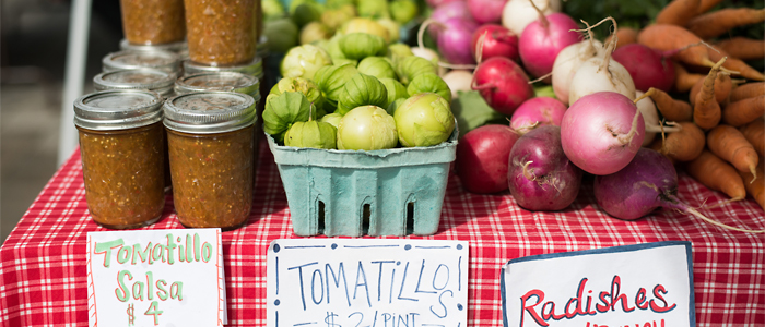 Photo of salsa, tomatillos, and radishes on sale at a farmer's market