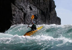 Photo of a kayaker on the ocean paddling in waves near a cliff