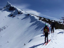 Photo of skiers following the ridge of a mountain