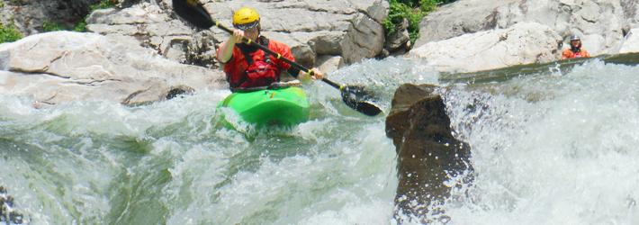 Photo of a kayaker kayaking through rapids on a rocky river