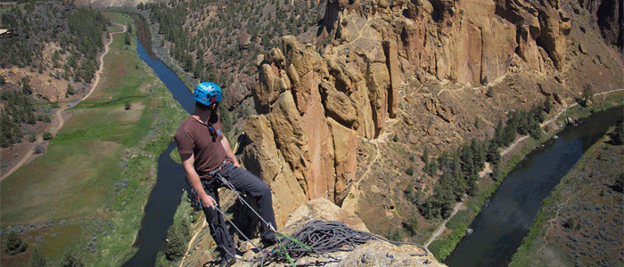 Photo of a rock climber on top of a cliff looking down at the valley and river below