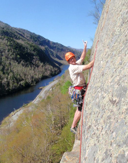 Photo of Will Roth rock climbing above a river