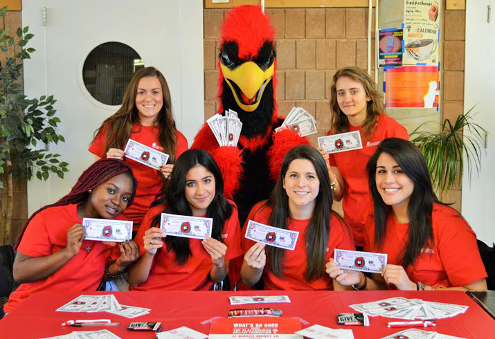 Photo of SUNY Plattsburgh students together with Burghy holding Burghy Bucks