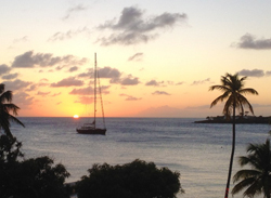 A sunset over a bay and sailboat near St. George University