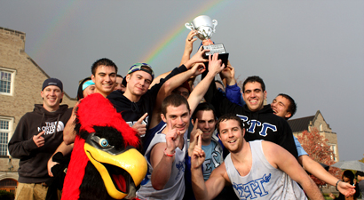 Sigma Tau Gamma holds up the winning cup by the pond under a rainbow