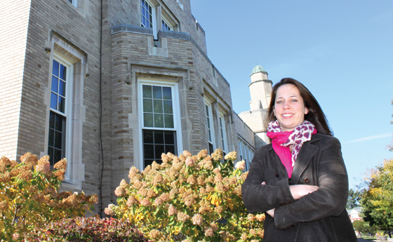 Photo of Alisa Woods standing in front of Hawkins Hall