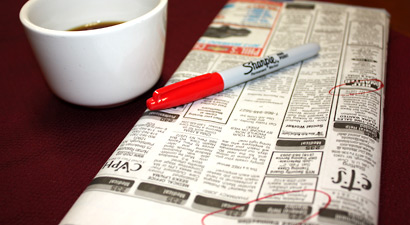 Photo of a cup of coffee and a newspaper's classified ads.
