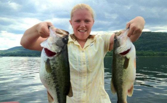 Photo of of Nikki Eddy holding 2 bass on a boat