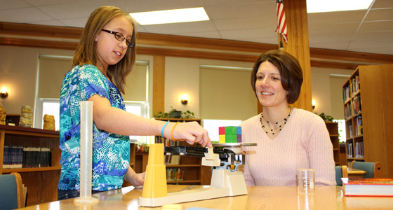 Photo of teacher Colleen Pandolph working with a student in class