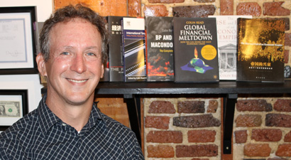 Photo of Professor Colin Read with books published by Department of Economics and Finance faculty.