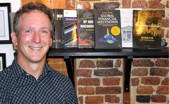 Dr. Colin Read standing in front of a collection of books recently published by SUNY Plattsburgh faculty