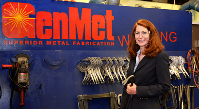 Photo of Mary Isbister in the GenMet factory  holding one of the tools they make there, in front of a GenMet sign and and tool rack.