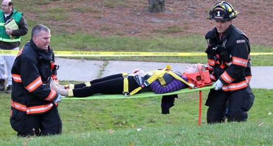 Photo of emergency personnel carrying a student in a neck brace on a stretcher to an ambulance.