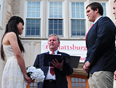 Photo of Zi Wang and Tim Maggio's wedding being officiated by Bill Laundry on the steps in front of Hawkins Hall