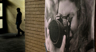 Photo of a photograph of a photographer taped to a hallway wall. The image is placed so the photographer appears to be taking photos of people walking by.