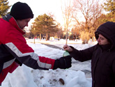 Photo of Ken Podolak and a student making slushies in a snowbank on campus.