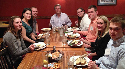 Photo of students and alumni networking and eating dinner at the Butcher Block.