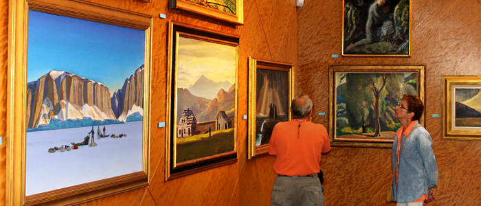 Photo of two people looking at paintings in the Rockwell Kent gallery